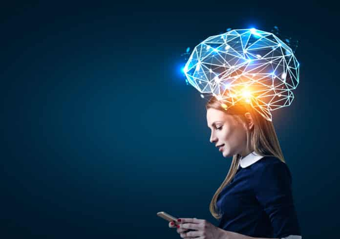 Side view of a blond businesswoman looking at her smartphone screen standing near a dark blue wall. There is a large blue brain hologram around her head.